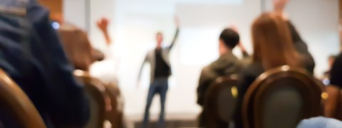 blurred group of people meeting in motivation seminar event at convention hall, speaker raising hand up and audience action follow , cheerful conceptblurred group of people meeting in motivation seminar event at convention hall, speaker raising hand up and audience action follow , cheerful concept